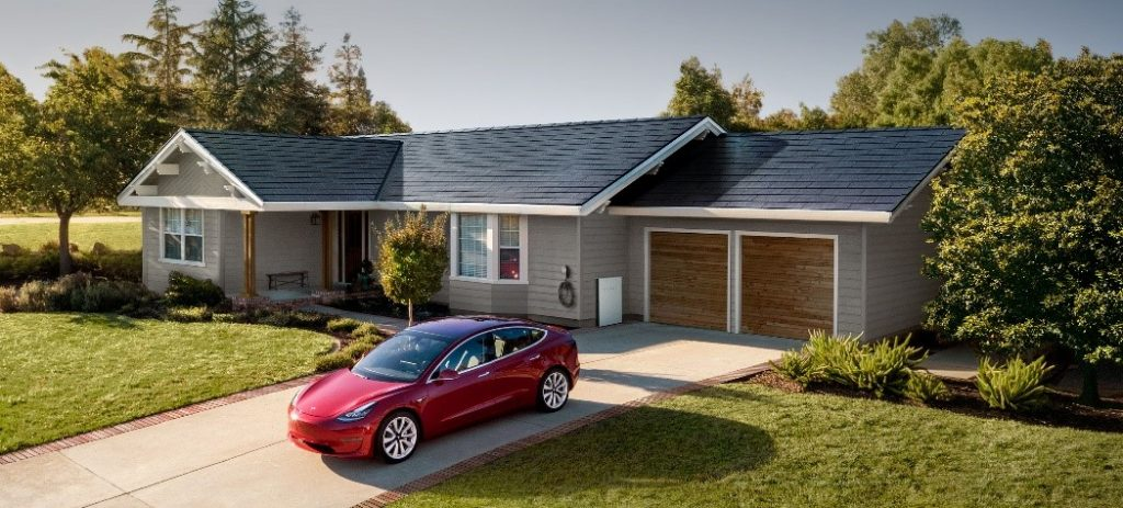 Tesla parked at a home with Tesla Solar Panels